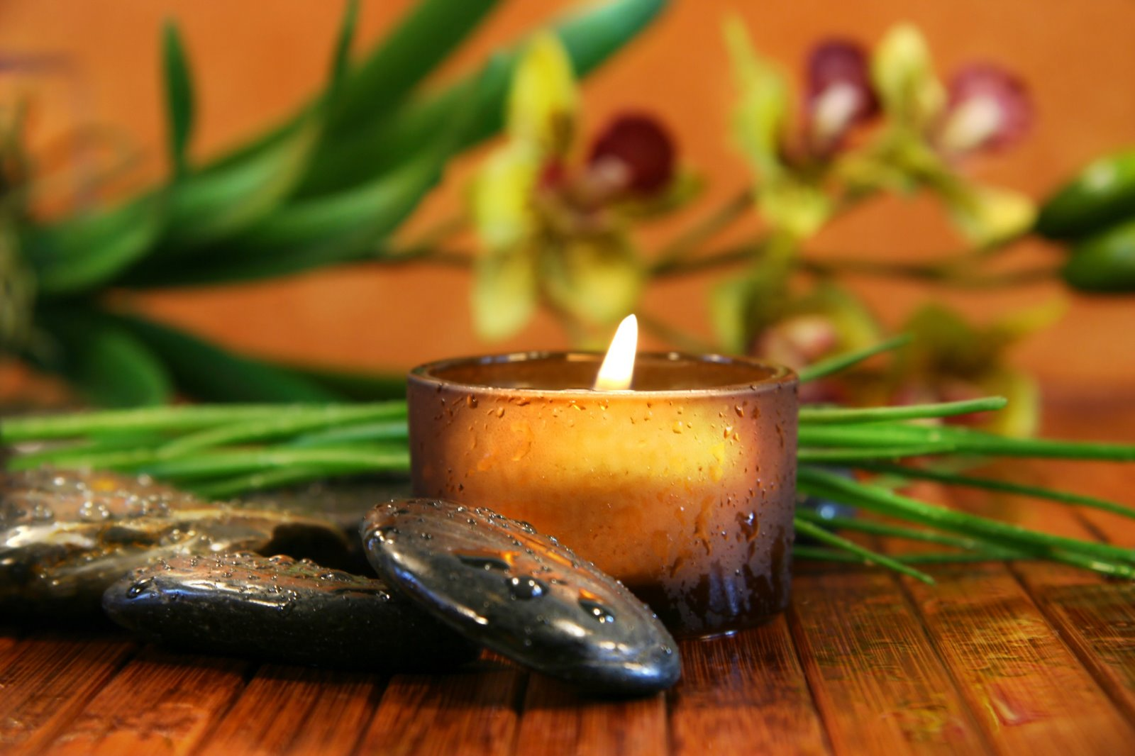 Amber candle and spa stones with orchid  on bamboo